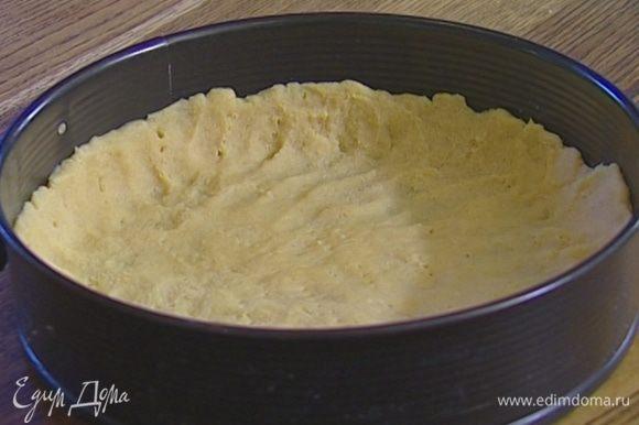 Охлажденное тесто выложить в разъемную форму для выпечки, равномерно распределить его, проткнуть в нескольких местах вилкой и застелить бумагой для выпечки.