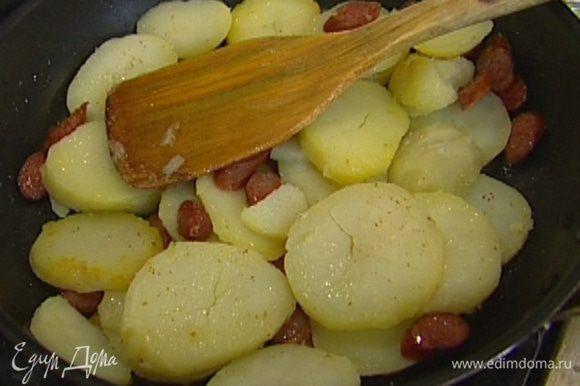 Разогреть в сковороде, которую можно ставить в духовку, растительное масло, обжарить картофель и колбаски до золотистого цвета, затем снять с огня.