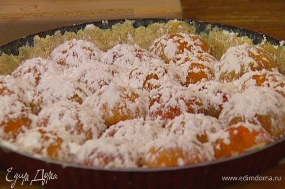 Плотно уложить половинки абрикосов на тесто срезом вниз, присыпать сахарной пудрой и выпекать в разогретой духовке 45 минут.