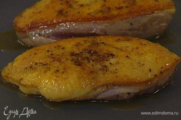Разогреть сковороду без масла и обжаривать утку по 4 минуты на каждой стороне до появления румяной корочки.