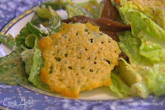 Разложить на листьях салата оставшиеся анчоусы и чипсы из пармезана.