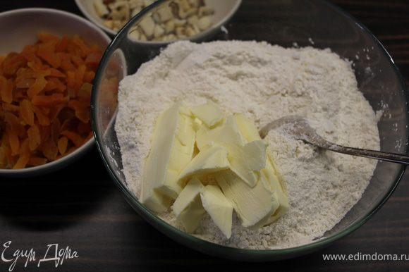 Добавить порезанное кусочками масло и, сначала ножом, а затем руками перетереть все в крошку.