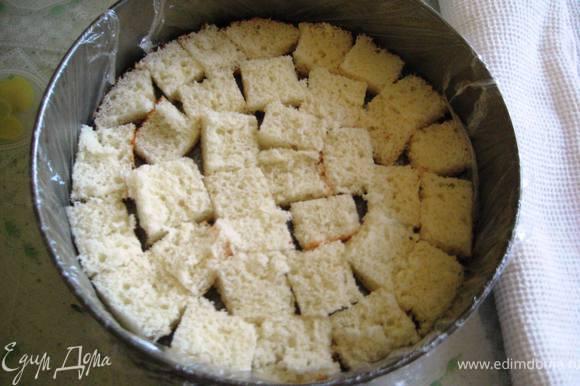 Разъёмную форму выслать пищевой плёнкой и выложить на дно бисквит.