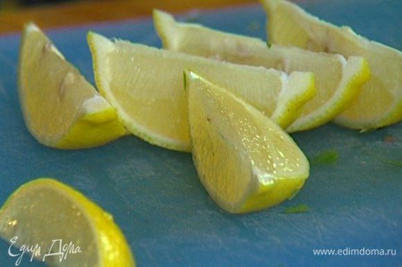 Лимон разрезать пополам, одну часть порезать на дольки, из другой отжать сок.
