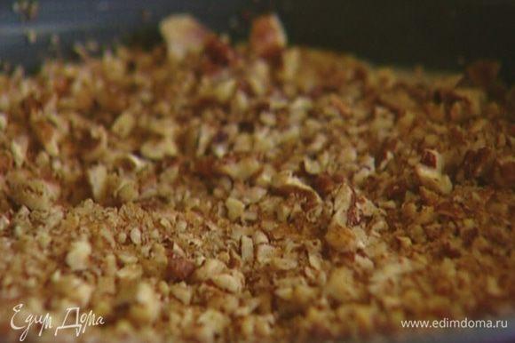 Разъемную форму для выпечки смазать сливочным маслом, выложить половину теста, а сверху — половину измельченных орехов с сахаром, затем равномерно распределить оставшееся тесто и снова орехи.