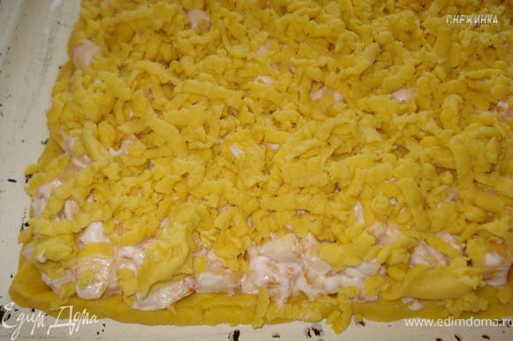 Начинку распределяем на раскатанное тесто, тесто из морозильника натираем на крупной тёрке поверх начинки.
