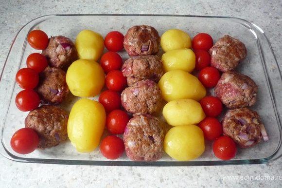 Картофеть почистить.Форму для запекания смазать маслом. Выложить в нее слоями картофель, тефтельки и томаты черри.
