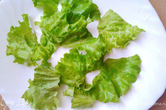 Листья салата помыть, высушить и порвать на дно салатницы.