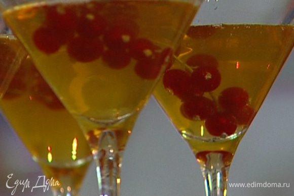 Разлить яблочный сок по прозрачным бокалам, добавить в каждый по веточке красной смородины и отправить на час в холодильник.