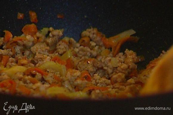 Мясо пропустить через мясорубку, выложить в сковороду к овощам, поперчить и обжаривать 7−10 минут, постоянно перемешивая фарш, чтобы не слипался.