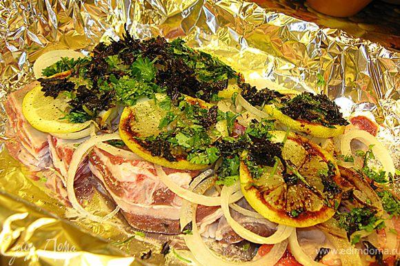 На противень щедро растилаем фольгу, я соединяла два полотна, чтобы было шире. Кладем первый слой бараньих ребрышек (кореечки), сверху нарезанные колечки лука, лимон (тоже колечками), нарубленную зелень, перчим, сбрызгиваем столовой ложкой соевого соуса.