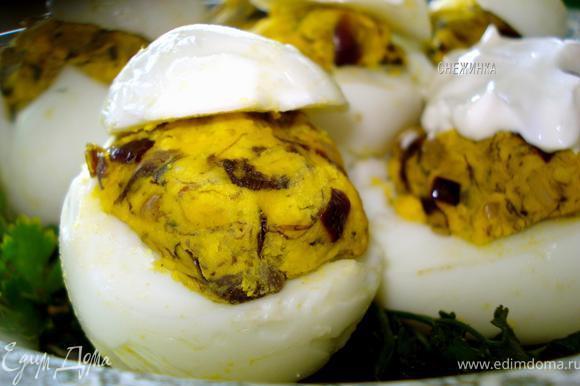Яйца (белки) аккуратно ложечкой наполнить получившимся фаршем. В салатник выложить зелень, затем на нее яйца, прикрыв «крышечками».