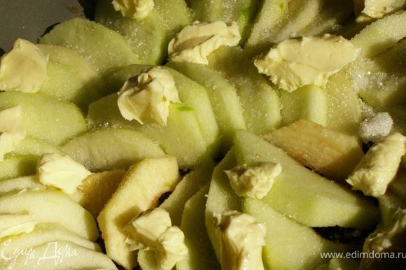 Посыпаем яблоки оставшимся сахаром, кладем по всей поверхности маленькие кусочки масла.