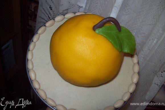 раскатываем желтый марципан и обтягиваем им торт, хвостики погибаем под донышко. приклеиваем палочку и листик. на час в холодильник.