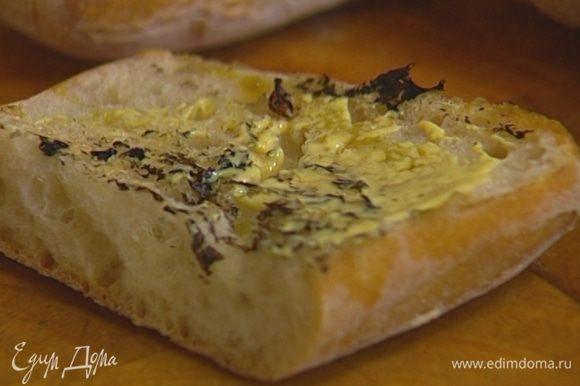 Чиабатту разрезать на 4 части, затем каждый кусок пополам вдоль. Прогреть на сковороде, где жарились котлеты, сбрызнуть обжаренную сторону хлеба оливковым маслом, смазать горчицей.