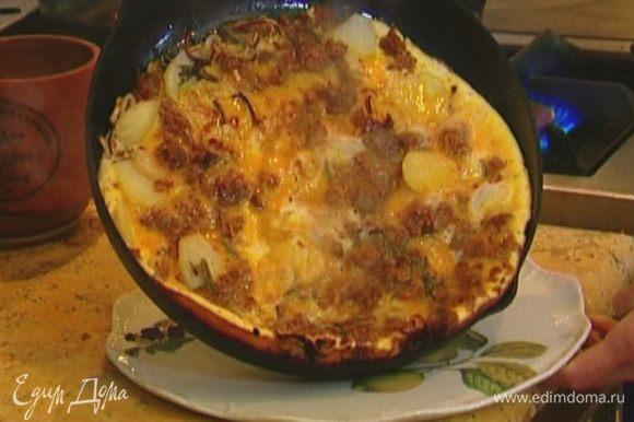 Выложить тортилью на большое блюдо, а затем вернуть на сковороду неподжаренной стороной вниз и держать на огне еще пару минут.