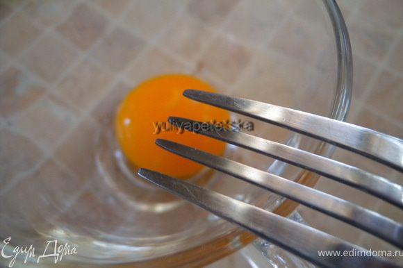 Взбить вилкой желток. Ввести его в смесь помешивая, еще немного прогреть (градусов до 60, до дымка).