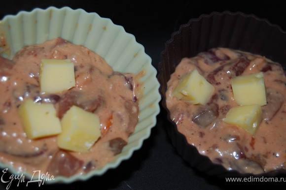 Выкладываем тесто в формочки. Если не силиконовые, смажьте сливочным маслом. По желанию можно добавить в серединку несколько кусочков сыра.