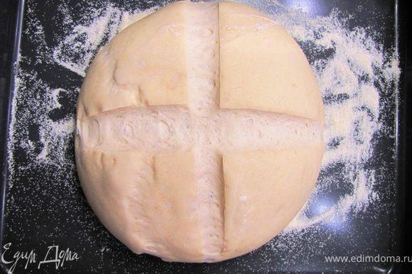 В это время нагрейте духовку до 230 градусов. Поставьте на дно духовки емкость с водой, чтобы духовка насытилась парами. Вода должна закипеть или по крайней мере от нее должен идти пар. Сделайте надрезы крест-накрест лезвием, чтобы хлеб не растрескался в процессе запекания.