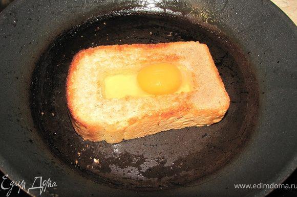 Возьмите небольшую сковороду с антипригарным покрытием. Налейте масло. Дайте нагреться. Положите хлеб, пару минут обжарьте на одной стороне, чтобы хлеб несколько поджарился. Переверните хлеб и сразу залейте яйца в отверстие. Разбивайте яйца аккуратно, чтобы желток не растекся (как для глазуньи). Сделайте огонь ниже среднего и обжаривайте пару минут. Посолите и поперчите яйца. У меня поместилось одно яйцо. Возможно у вас поместится два. Главное, чтобы все отверстие заполнилось.