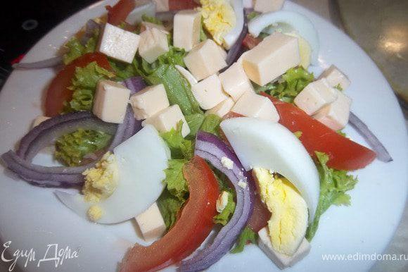 Выложить на тарелку поверх салата нарезанные сыр и яйца.