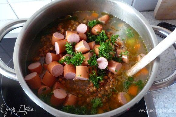 Добавить чечевицу с сосисками и петрушкой в суп, дать закипеть и потомить еще минут 5. При необходимости добавить горячей воды.