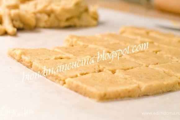Разогреть духовку до 180C.Раскатать тесто высотой 4 мм.Разрезать на ромбы/квадраты размером 3х3 см.Смазать печенье яйцом,выпекать 15 мин.