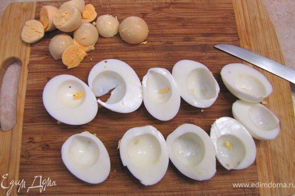 Разрежьте яйца пополам и вытащите желтки. Их можно будет просто раскрошить в бульон. Нарежьте белки кубиками размером с горошину.