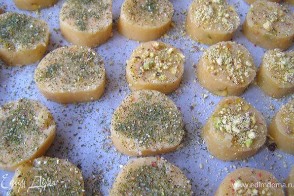 Холодное тесто нарезать кружками толщиной 1 см. Выложить печенье на лист, покрытый бумагой для выпечки. Смазать верх белком. Печенье БЕЗ фисташек посыпать смесью перцев и травами, остальное - измельчёнными фисташками.