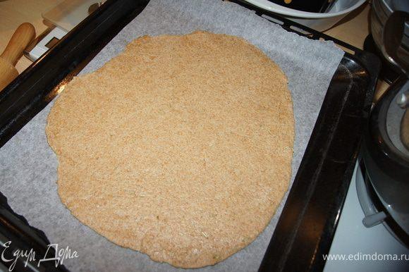 Духовку нагреть до 200С. Противень застелить пергаментом. Тесто раскатать толщиной 0,5 см. Аккуратно переложить тесто на противень.
