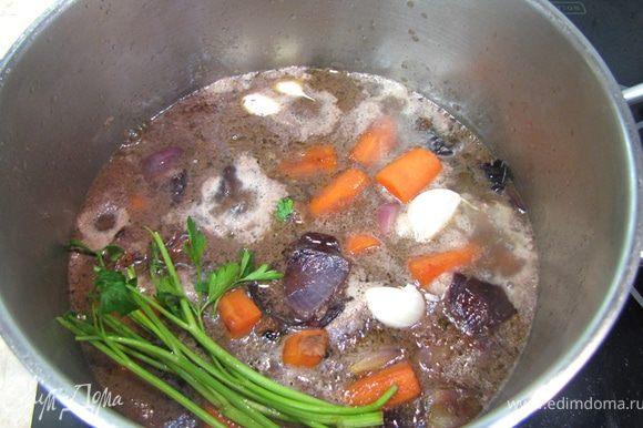 Кладем обратно овощи в мясо, заливаем маринадом, бульоном и четырьмя ложками коньяка. Кладем травы, чеснок.
