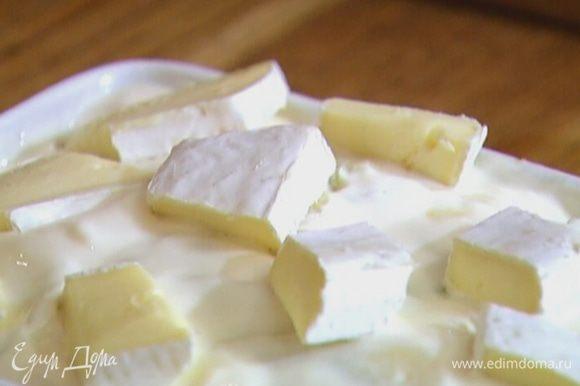 Выложить на запеканку сметану, сверху разложить кусочки сыра.