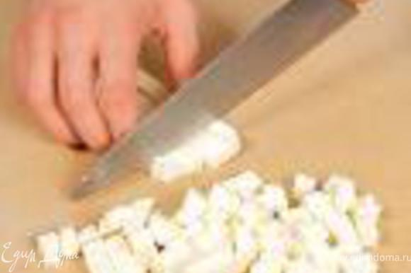 Брынзу нарезать кубиками. Выложить в салат. Салат полить заправкой и украсить свежей зеленью кинзы.