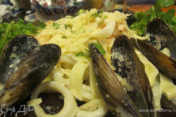 За 2 минуты до готовности слить пасту и добавить ее к морепродуктам.Тщательно перемешать.Подавать пасту сразу же щедро присыпав пармезаном и свежемолотым черным перцем.В тарелку выложить рукколу и сбрызнуть оливковым маслом. приятного аппетита!