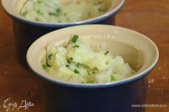 Небольшие керамические формочки смазать внутри оливковым маслом, обсыпать измельченными хлопьями, выложить в них картофельную массу и сделать посередине небольшое углубление.