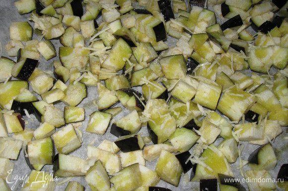 Баклажан режем кубиком, кладем на протвень, застеленный пекарской бумагой, сбрызгиваем оливковым маслом, посыпаем крупной солья и крошим 2-3 зубчика чеснока