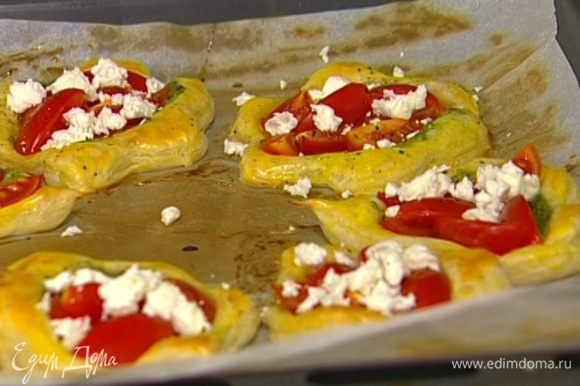 Как только тарталетки начнут румяниться, вынуть противень из духовки, положить на каждую тарталетку по нескольку кусочков феты и вернуть в духовку еще на пару минут.