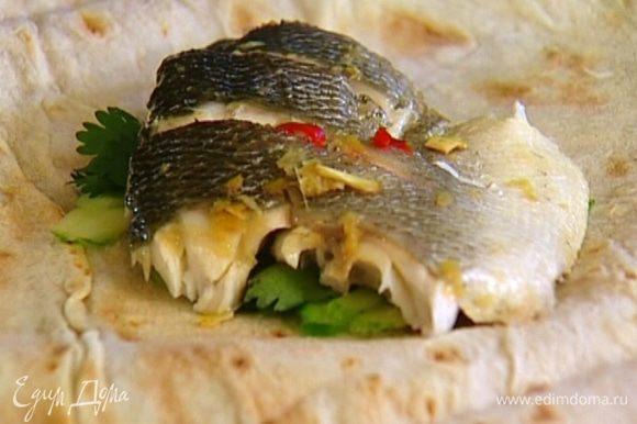 Лаваш разделить на части, выложить на каждую немного нарезанного огурца, кусок запеченной рыбы и пару веточек кинзы. Свернуть конвертиками.