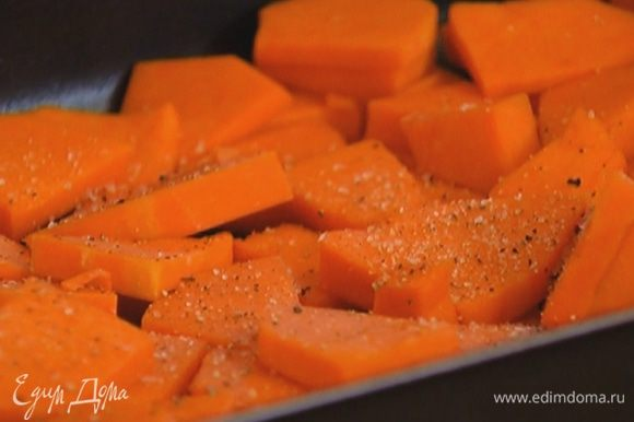 Выложить тыкву в небольшой противень, посолить, поперчить, сбрызнуть оливковым маслом, перемешать и отправить в разогретую духовку на 15 минут.