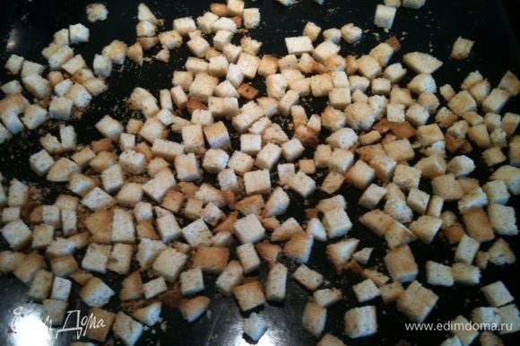 В духовке приготовить сухарики, порезав белый хлеб на кубики...