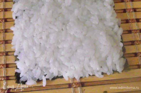 Распределить рис чуть больше половины смачивая руки в лимонной водичке, чтобы рис не прилипал.