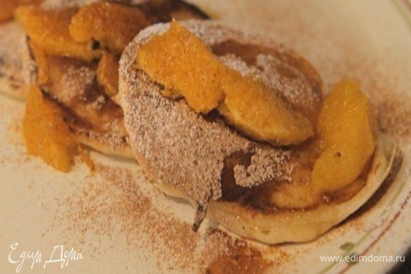 Подавать оладьи с апельсиновым соусом, посыпав их сахарной пудрой и корицей.