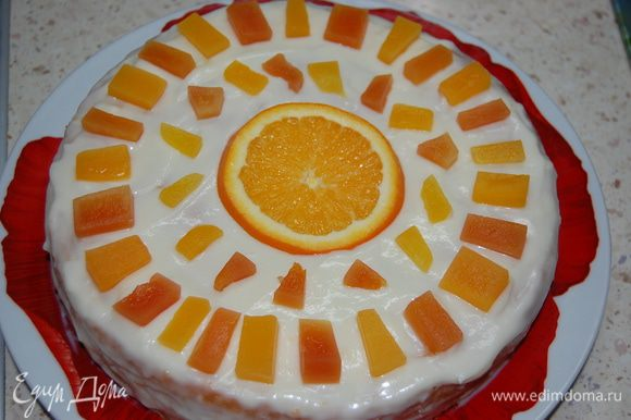 Накрыть вторым коржом, намазать оставшимся кремом. Сверху выложить кусочки фруктов.
