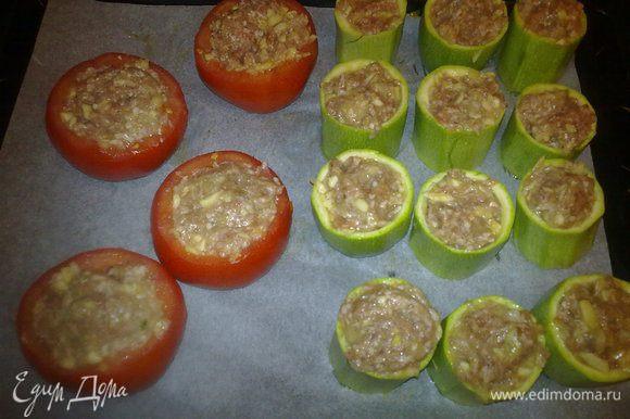 Кабачки разрезаем на три-четыре части. Вычещаем сердцевину и добавляем ее в свиной фарш, солим, перчим. Из помидор также вычещаем середину. Наполняем овощи полученым фаршем. Запекаем в духовке до готовности.