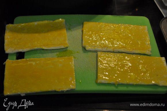 Подготовить 2 противня застелив пергамент.бумагой для выпечки. Выложить тесто из упаковки слегка присыпать мукой.Смазать яйцом.