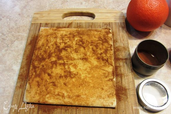 Разморозьте тесто. Для этого я положил тесто на разделочную доску и накрыл пакетом. Посыпьте сверху на тесто корицу и распределите пальцами по поверхности