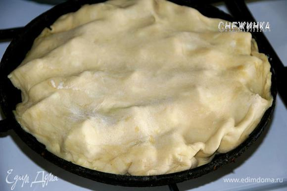 Слоеное тесто раскатать на присыпанной мукой поверхности в круг, чтобы он был чуть шире сковороды и толщиной где-то 3 мм. Накрыть яблоки тестом, слегка подоткнув края. Сковороду поставить на маленький огонь (кто использует форму, так не делает) на 5 минут, чтобы сахар с маслом прогрелся и начал карамелизоваться.