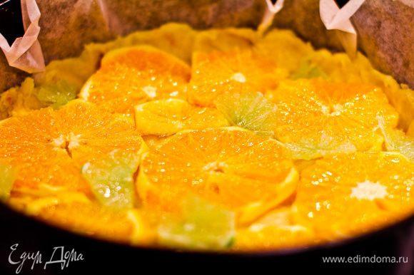 Всыпьте муку и апельсиновую цедру, замесите тесто. Разделите тесто на две неравные части. Застелите форму пергаментом. В форму выложите большую часть теста, разровняйте, сделайте бортик. На ней разместите кружочки апельсина и лайма.