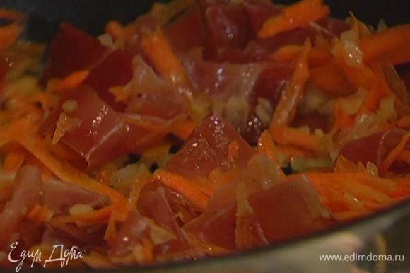 Ветчину нарезать тонкими полосками, добавить к луку с морковью и обжаривать все до готовности лука.