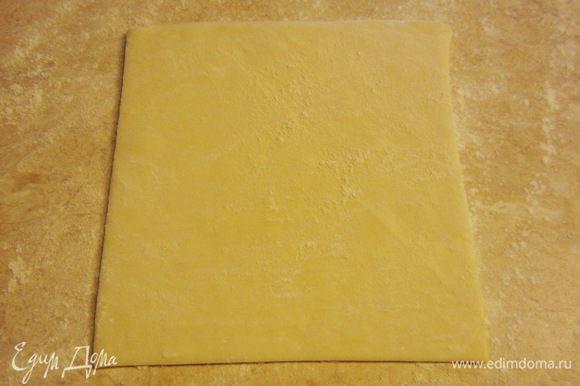 Посыпьте стол мукой и положите один размороженный пласт теста.